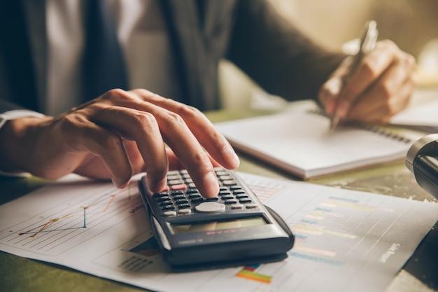 Бизнесмен с калькулятором подсчета заметок в руке офиса пишет в блокноте