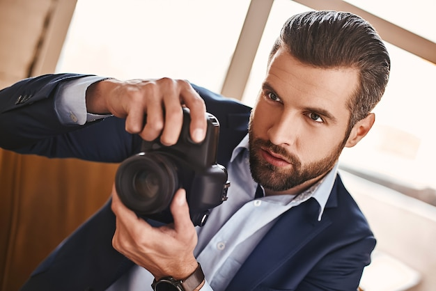 Businessman with a camera young bearded and stylish man is taking photos on camera while
