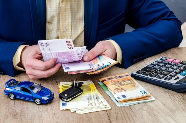 Businessman with car model and money