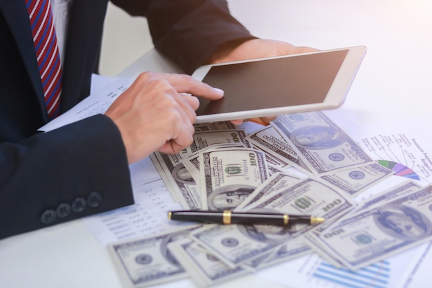 Businessman with cash dollars - business concept, tablet and finance.