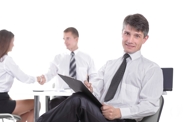 Businessman with clipboard sitting at his desk