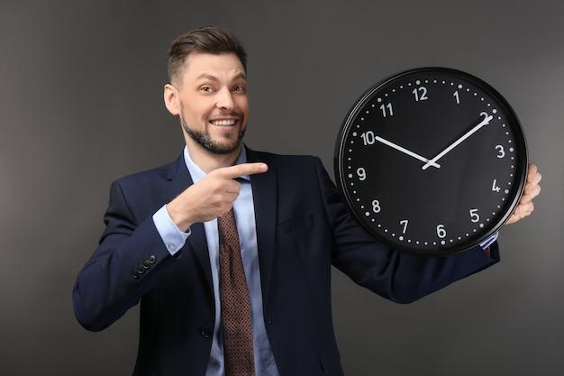 暗闇の中で時計を持つビジネスマン。時間管理の概念