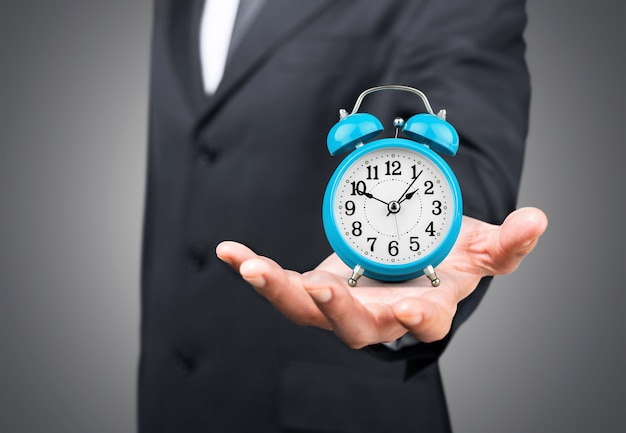 Businessman with clock in time concept on background