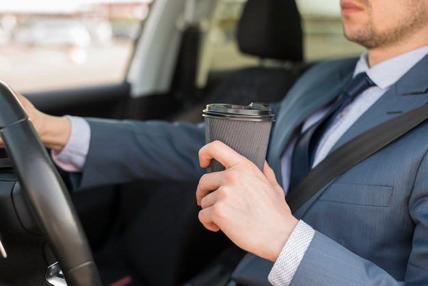 Businessman with coffee cup in car