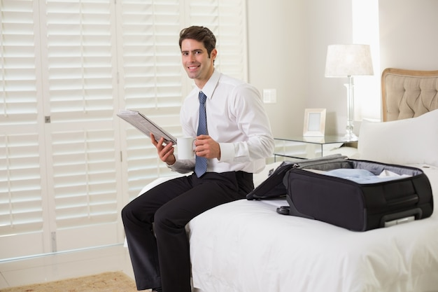 Businessman with coffee cup and newspaper by luggage at hotel room