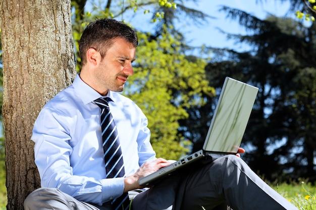 Бизнесмен с компьютером в парке летом