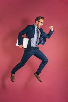 Businessman with computer jumping