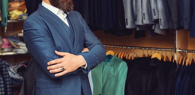 ジャケットの近くに自信のある顔を持つビジネスマン。ハンガーでスーツを着たひげを持つ男。スーツを着たハンガーの近くの店員または売り手。モダンなスタイル。エレガントな服。男性のファッション業界。