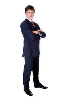 Businessman with crossed hands standing against isolated wall