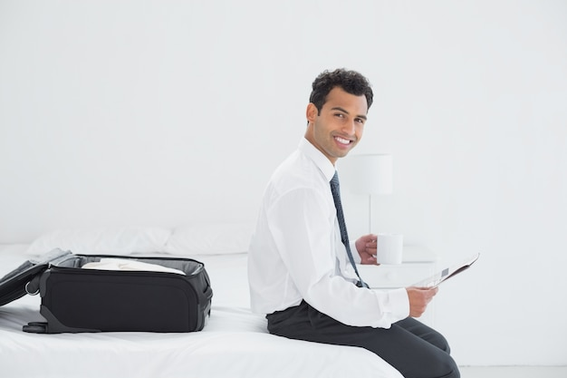 Businessman with cup and newspaper by luggage at a hotel room