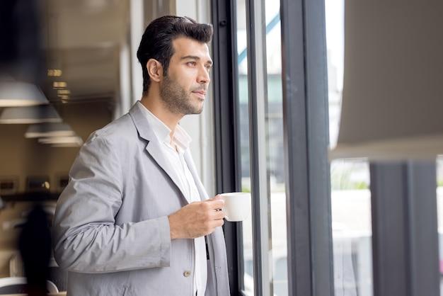 Бизнесмен с чашкой кофе, глядя из окна в офисе