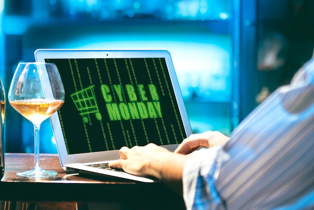 Businessman with cyber monday advert on the laptop screen on the desk