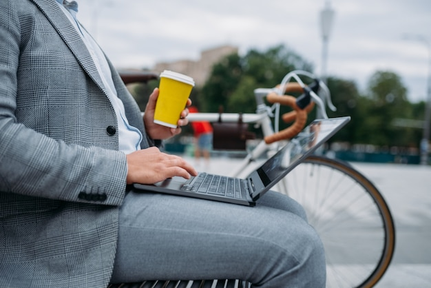 Businessman with cycle drinks coffee on the bench at the office building in downtown.