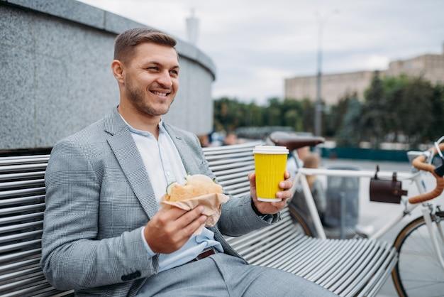 사이클 사업가 시내에서 사무실 건물 벤치에서 점심을 먹는다.