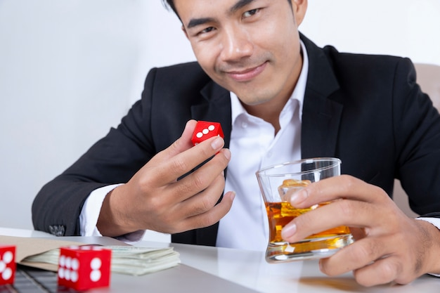 Businessman with dice on hand with glass of liquor and money gambling addiction concept.