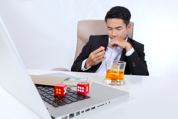 Businessman with dice on hand with glass of liquor and money, gambling addiction concept.
