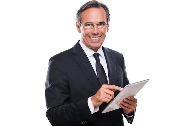 Бизнесмен с цифровым планшетом. уверенный зрелый мужчина в формальной одежде работает на цифровом планшете и улыбается, стоя на белом фоне
