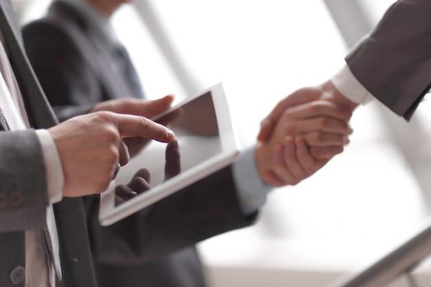비즈니스 파트너의 악수를 배경으로 디지털 태블릿을 사용하는 사업가입니다.