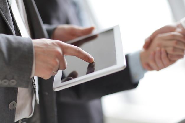 비즈니스 파트너의 악수의 배경에서 디지털 태블릿 사업.