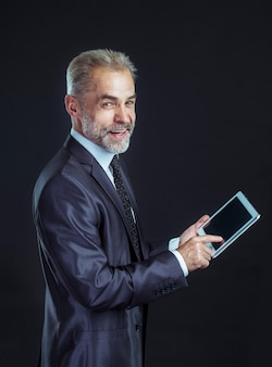 Бизнесмен с цифровым планшетом на черном фоне.