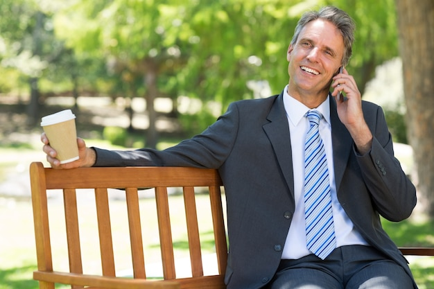 Businessman with disposable cup answering cellphone