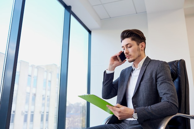 Businessman with documents hands of talking on a cell in modern