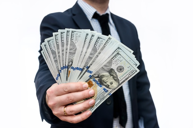 白で隔離されるドル紙幣を持ったビジネスマン