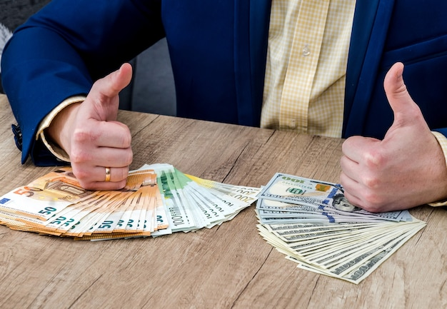 Businessman with dollar and euro banknotes thumbs up