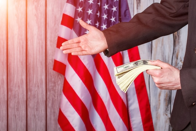 Бизнесмен с долларами давая руку. флаг сша, человек и деньги. какой дружеский жест. партнерство - это сила.