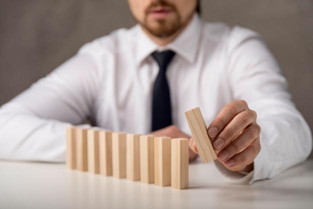 Uomo d'affari con pezzi di domino