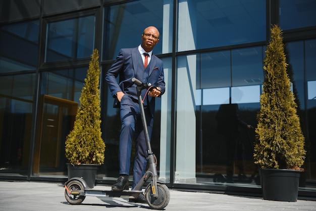 Бизнесмен с электрическим скутером, стоящим перед зданием современного бизнеса, говорящим по телефону.