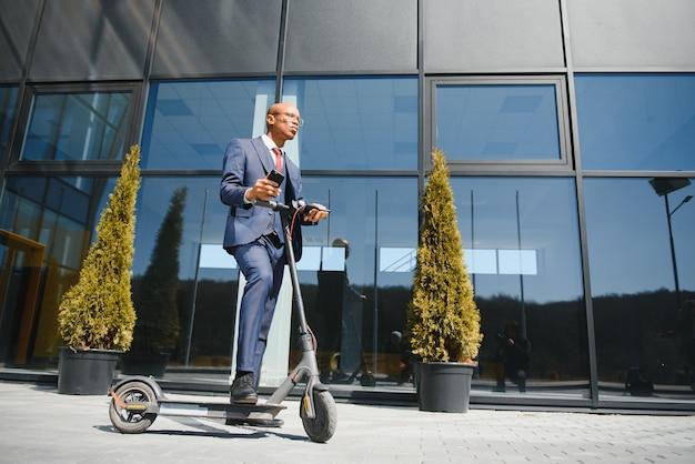 電話で話している現代のビジネスビルの前に立っている電動スクーターを持つビジネスマン。
