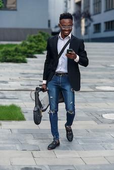 歩く電動スクーターを持ったビジネスマン