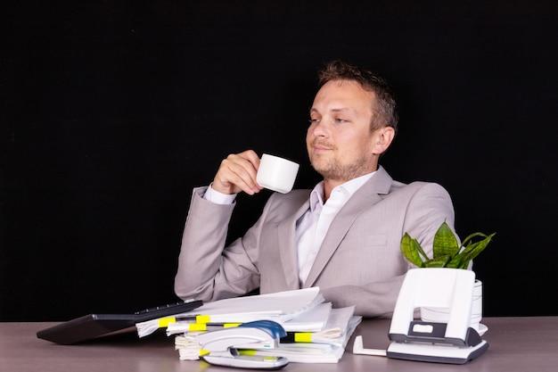 彼の顔に感情を持ったビジネスマンはコーヒーを飲んでいます。