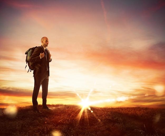 Бизнесмен с рюкзаком исследователя ищет новый бизнес