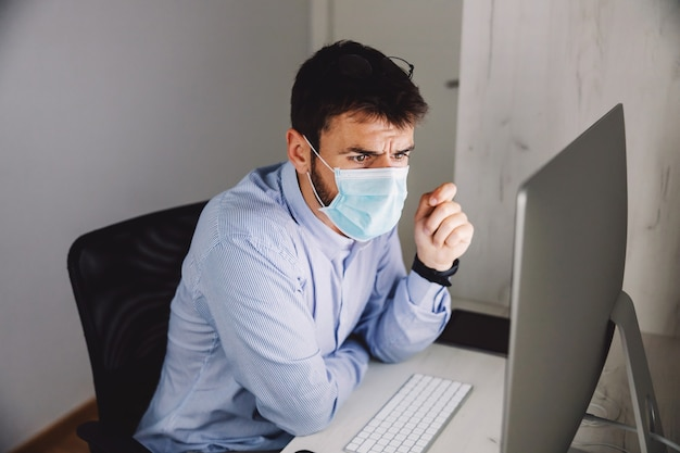コロナウイルスの間に彼のオフィスに座って、コンピューターを見てフェイスマスクを持つビジネスマン