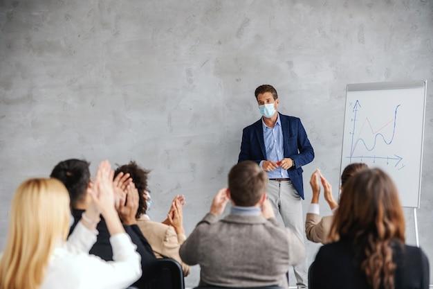 Бизнесмен с лицевой маской, стоящей в зале заседаний и имеющей представление фондовой зарплаты.