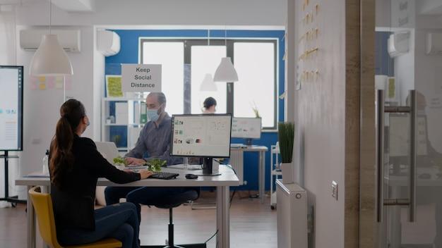 Бизнесмен в маске трогает локтем своего коллегу, чтобы избежать заражения коронавирусом. сотрудники поддерживают социальное дистанцирование во время работы над проектом коммуникационной компании.