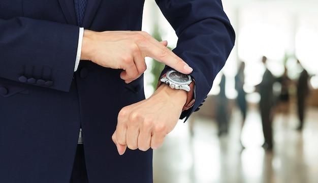 彼の手で彼の時計に指を指すビジネスマン。右側に