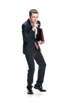 Бизнесмен с папкой, просящей тишины, изолированной на белой стене