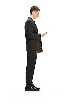 Uomo d'affari con cartella in chat sullo smartphone isolato sul muro bianco