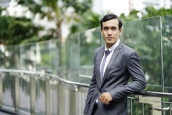 フォーマルなスーツと屋外近代的な都市の背景に立っているビジネスマン。男の笑顔とlookin