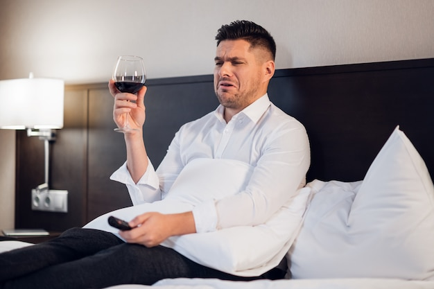 Businessman with a glass of red wine in bed, watching tv, making a funny face as if he sees something disgusting on tv