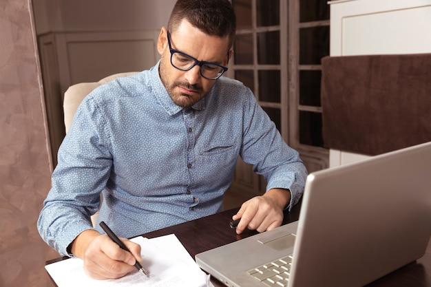 自宅から彼のラップトップで作業している眼鏡とシャツを持つビジネスマン