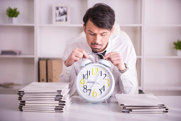 Businessman with glasses on forehead is holding the clock.