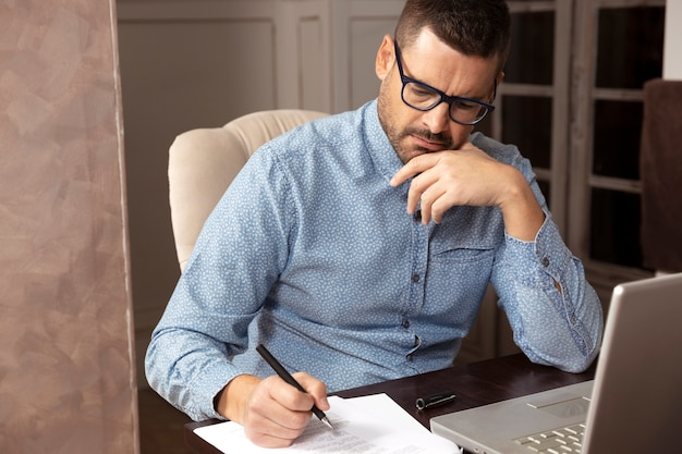 Businessman with glasses and shirt working on his laptop from home