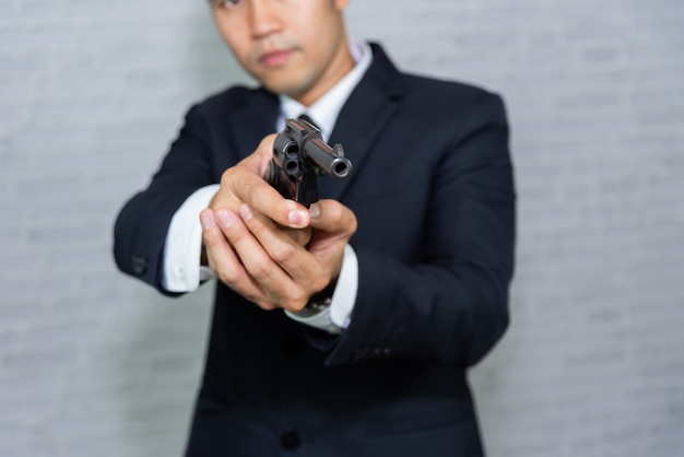 Businessman with gun on gray background