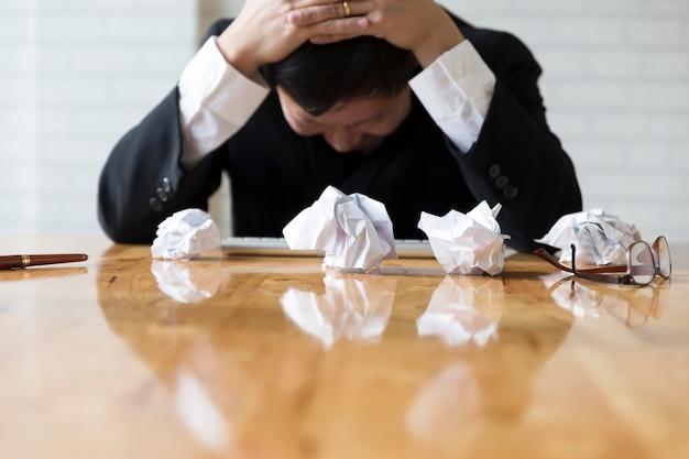 Бизнесмен с рукой на голову в офисе - расстроен, разочарование, стресс концепции