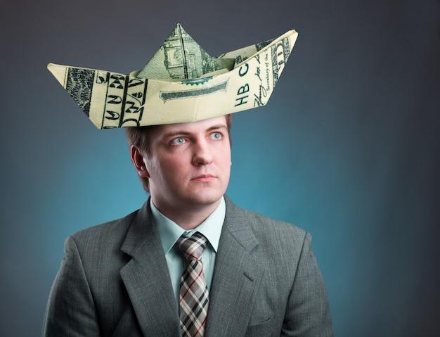 Бизнесмен в шляпе корабля из денег, изолированных на сером