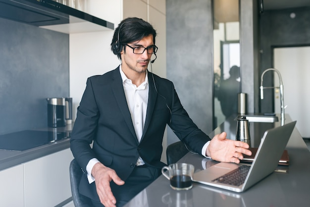自宅のコンピューターからのビデオ会議でヘッドセットを持つビジネスマン Premium写真